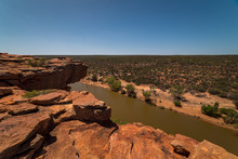 Panoramic View Overlooking Red Colored Rocks With A Large River Below And A Desert Landscape In The Background In Kalbarri, Western Australia.