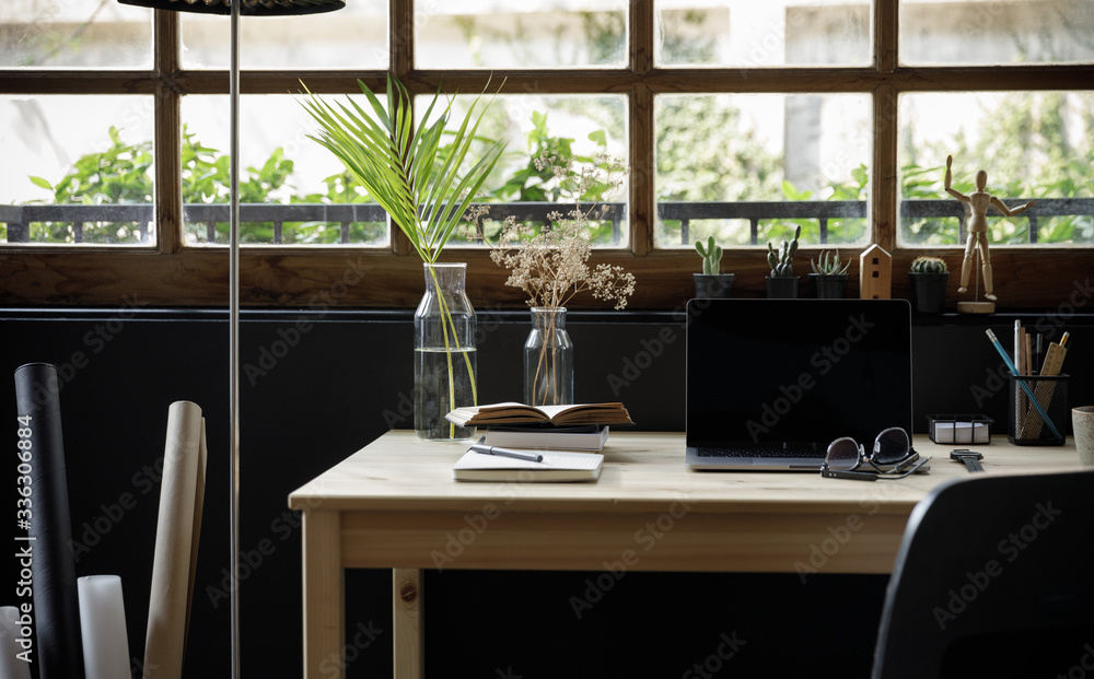 Modern home office creative space perfect for working from home lifestyle with laptop on the desk and sofa in the living room, Quarantine isolation during the Coronavirus (COVID-19) health crisis
