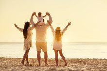 Family Of Four Peoples With Raised Arms At Sunset Beach