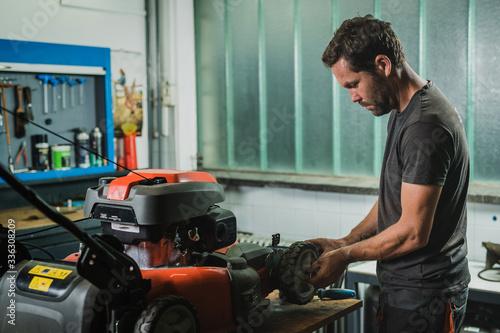 Fototapeta Professional serviceman is repairing a lawnmower, refitting a front wheel. Man repairing a mower in a workshop obraz