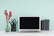canvas print picture - Modern business interior - workplace with blank computer display, black stationery, books, red branch in light green mint menthe interior on white wood desk.