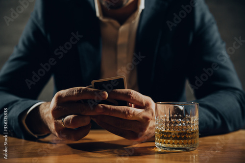 Photo Close up of man playing card and drinking whisky.