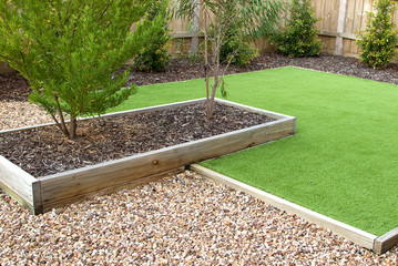 Combination of timber, plants, artificial grass, decorative gravel and mulch
