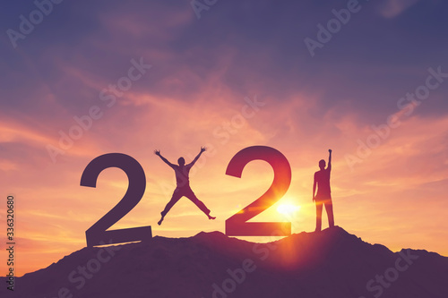 Cuadros en Lienzo Man raise hand up and man jumping on sunset sky at top of mountain and number like 2021 abstract background