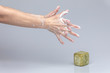 White people's hands washing each other with green foamy Marseille's soap isolated in front of a grey background with structurant lights and shadows