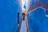 Fototapeta Uliczki - Indian women in traditonal india dressed Indian Saree walking through the narrow blue streets of the blue city of Jodhpur, Rajasthan, India.