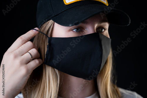 Fotografie, Obraz The girl puts a protective black mask on her face to protect her from the coronavirus