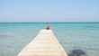 Teenager sits on the edge of wooden pier against the backdrop of beautiful azure sea, slow-motion video.