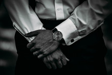 A Classy Groomsman With Left Hand Over Right While Wearing A Nice Watch