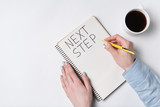 NEXT STEP Notice in notepad on white background. Words handwritten. Women's hands, cup of coffee and Notebook