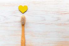 Wooden Bamboo Toothbrush With Wooden Heart On Wood Background With Copy Space