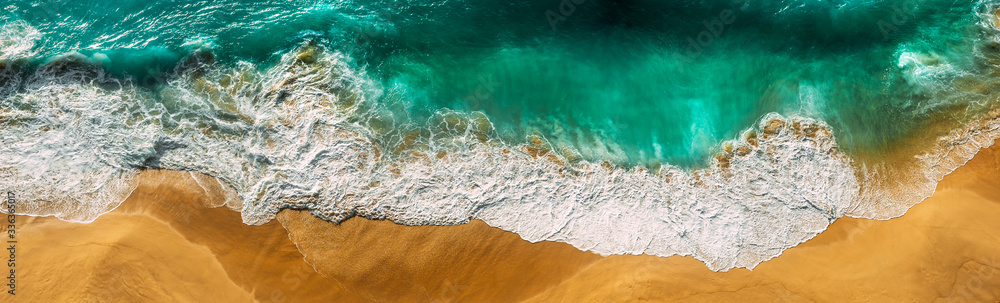 Fototapeta Beautiful sea wave at sunset from a bird's eye view. Beautiful lonely beach at sunset. Aerial view of turquoise ocean waves in Kelingking beach, Nusa penida Island in Bali, Indonesia. Beaches of Bali