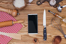 Various Kitchenware Utensils And Smartphone With Empty Screen On The Wooden Background