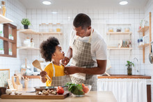 Happy Family With African Father And Son Dress Up Together Before Cooking In The White Kitchen. Single Dad Chef With Black Kid Helper In Yellow Shirt Preparing Food And Looking At Each Other At Home.