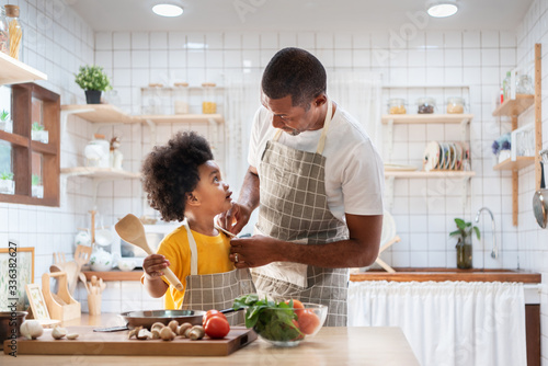 Happy family with African father and son dress up together before cooking in the white kitchen Fototapeta