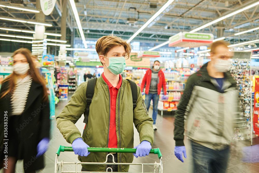 Fototapeta man in mask and protective gloves buying in shop at coronavirus epidemic