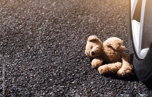 Lonely teddy bear with sad face lying next to the tyre, Brown bear falling down next to wheel with bright light on spring or summer. International missing children's day. Domestic Violence concept