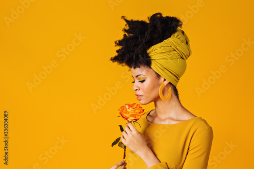 Obraz Profile portrait of a beautiful young woman smelling yellow orange rose and looking down, isolated on yellow background - fototapety do salonu