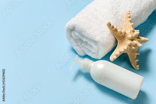 White towel, bottle with massage oil dispenser and starfish on a gobble background Slika na platnu