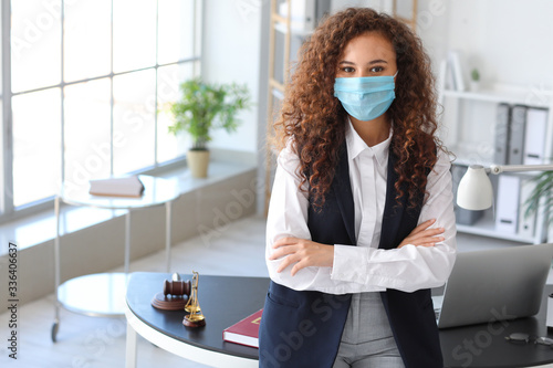 Fotografia Female lawyer in protective mask working in office