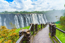Walking Way With View To The Dramatic Clouds And Waterfall At Victoria Falls On The Zambezi River, Zimbabwe, Zambia.