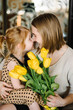 Cute little girl greeting mother and gives her a bouquet of flowers tulips at home. Mother's day concept. Mom and daughter smiling, hugging and kissing. Happy family holiday and togetherness.