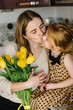 Cute little girl greeting mother and gives her a bouquet of flowers tulips on kitchen and kissing. Mother's day concept. Mom and daughter smiling. Happy family holiday and togetherness.