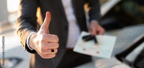 Fotografie, Obraz Autokauf, Verkäufer hält Zulassung Papiere und Schlüssel vor einer Reihe an Neuw
