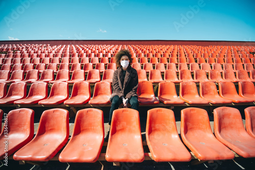 Curly girl in a surgical mask sitting in an empty stadium during epidemic disease Covid-19 Canvas