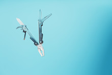 The Multitool Multi-function Tool Hovers On A Blue Background. The Concept Of An Expanded Multi-tool With Free Space.