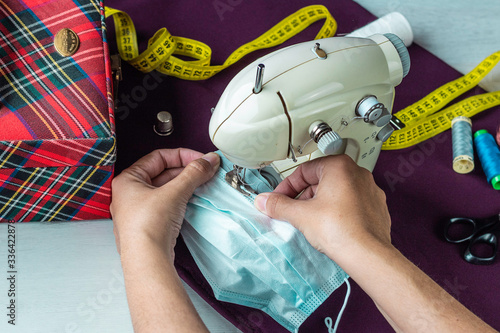 Photo Female hands sewing homemade surgical masks Conceptual health emergency, action