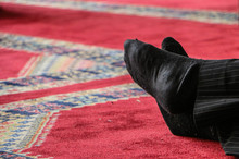 Close-up Of Legs Crossed At Ankle On Carpet