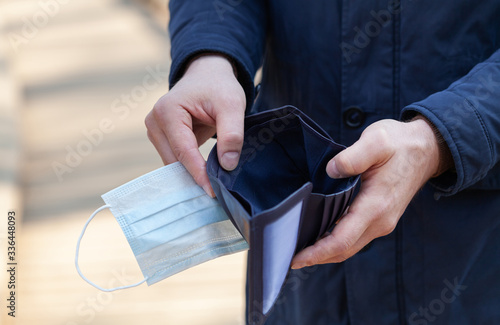 Valokuvatapetti Man holds a medical mask and empty wallet without money