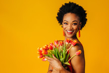 Portrait Of A Happy Young Woman With A Bouquet Of Orange Tulips And  Beaded Earrings Looking At Camera
