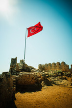 Turkish Flag Flying On Top Of The Byzantine Castle In The Town Of Kaleköy On The Mediterranean Sea, Turkey