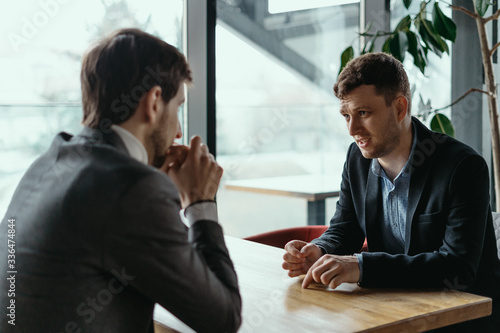 Obraz Focused businessman listening to business partner talking during discussion, thinking over his ideas while sitting at the table - fototapety do salonu