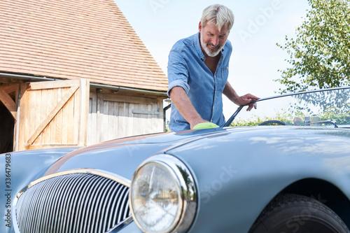 Fototapeta Mature Man Polishing Restored Classic Sports Car Outdoors At Home obraz