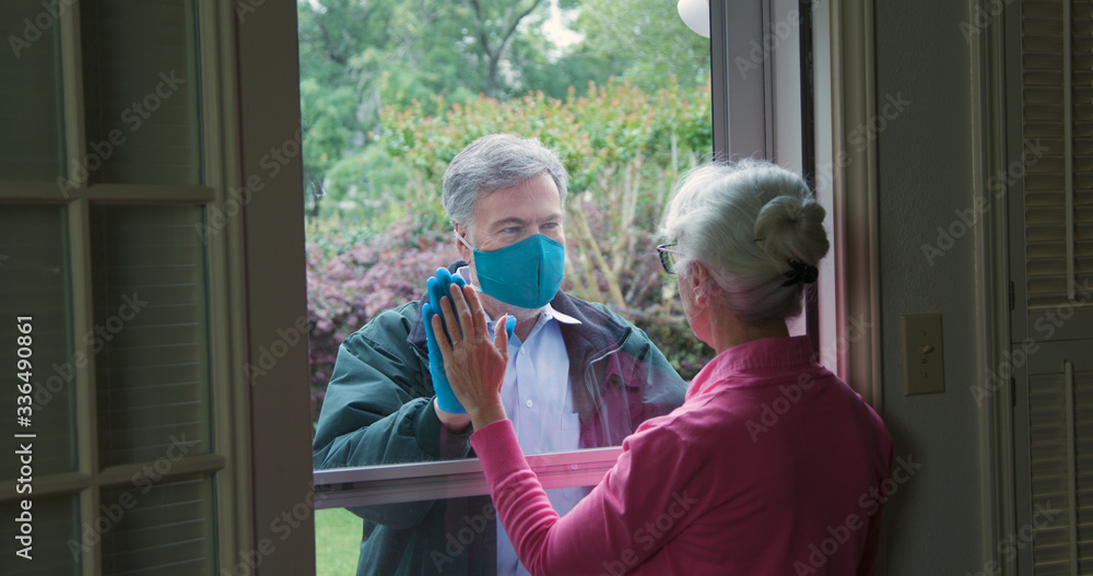 Fototapeta A mature man lovingly checks on an elderly relative but follows the social distancing mandate issued due to COVID19 by not entering her home.
