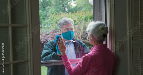 Obraz na płótnie A mature man lovingly checks on an elderly relative but follows the social distancing mandate issued due to COVID19 by not entering her home