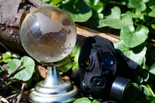 A Small Glass Globe And A Gas Mask In The Green Grass.
