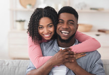 Loving African American Couple Hugging At Home And Looking At Camera