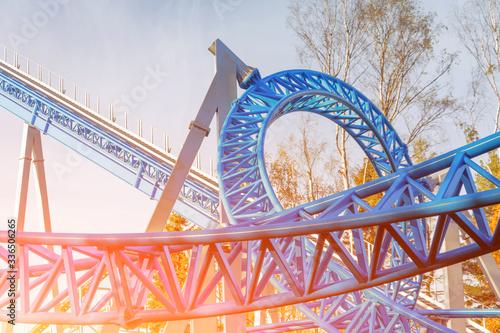 Fototapeta Loop and turn on a blue roller coaster in an amusement park obraz