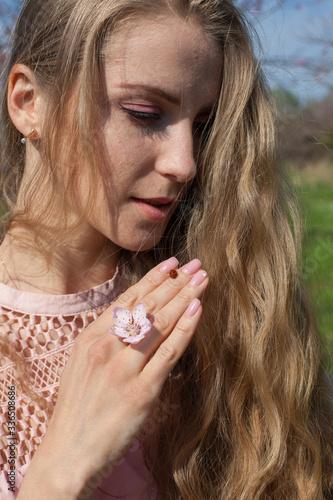 Fotografija Beautiful blonde woman in pink dress and ladybug insect
