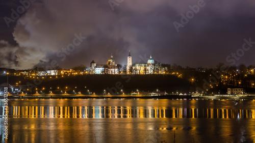 Obraz Oświetlony zamek nad rzeką z odbiciem neonów w wodzie. - fototapety do salonu