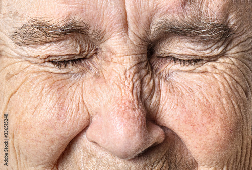 Wrinkled old face close up. Portrait of an old woman with closed eyes.