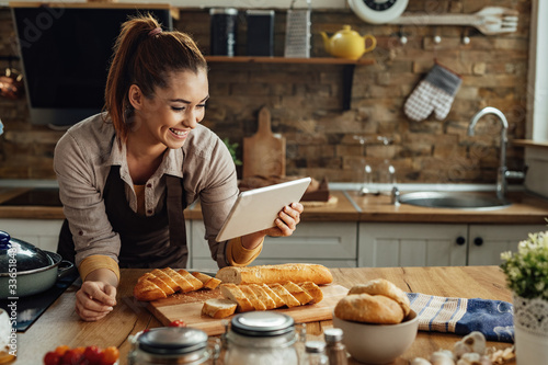 Fotomural Happy woman reading recipe on touchpad while preparing food in the kitchen