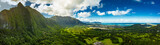 A Panoramic aerial image from the Pali Lookout on the island of Oahu in Hawaii.  With a bright green rainforest, vertical cliffs and vivid blue skies.