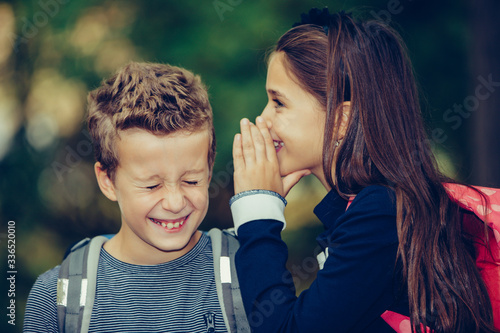 Small girl whispering something in an ear of her friend with smile and laugh Wallpaper Mural