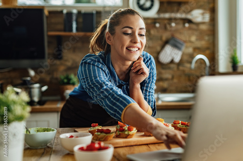 Happy woman surfing the net on laptop while preparing bruschetta in the kitchen.