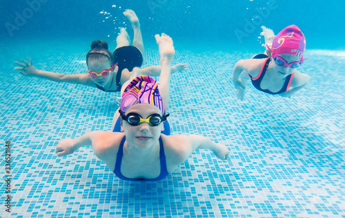 Obraz Underwater photo of young friends in swimming pool. - fototapety do salonu